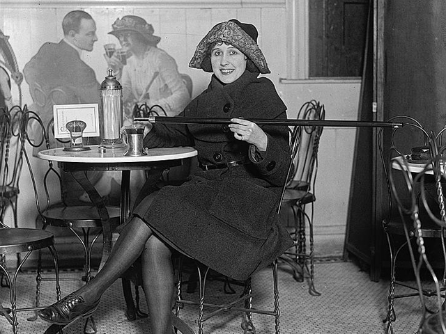 Woman pouring alcohol from a cane into her Coca-Cola.